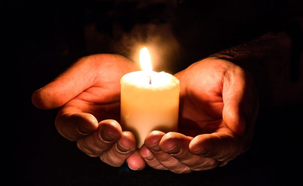 A small candle held in cupped hands.