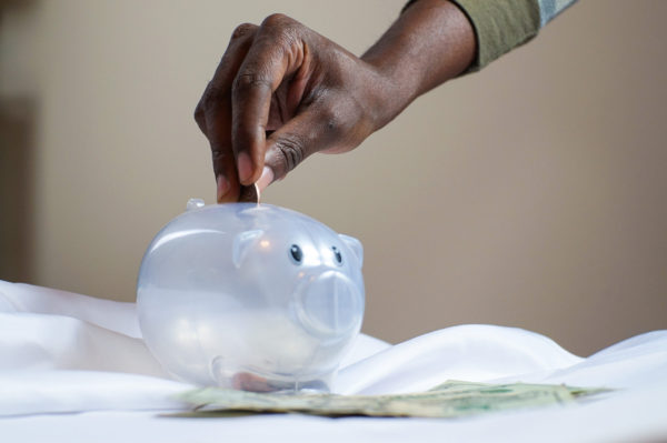A hand placing a coin in a translucent piggy bank.