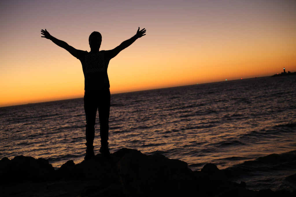 A silhouette of a person, arms raised, standing against a sunset over a lake.