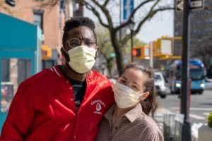 Two people wearing masks outdoors, arms around each other, looking at the camera, outdoors.