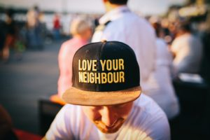 """A person in a black ball cap with the words """"love your neighbour""""."""