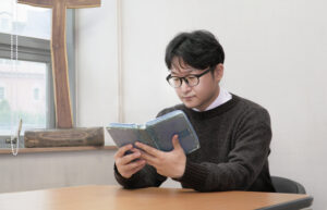 A young minister with black hair and glasses is seen seated at a table, holding and reading a bible.