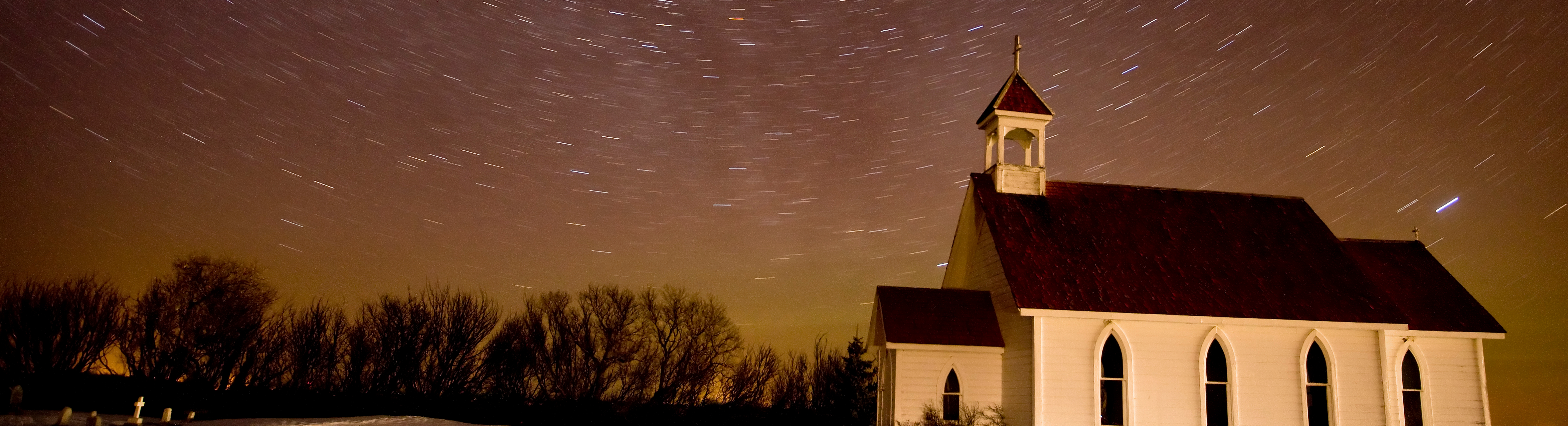 White country church with trees along the bottom and night sky with star trails above.